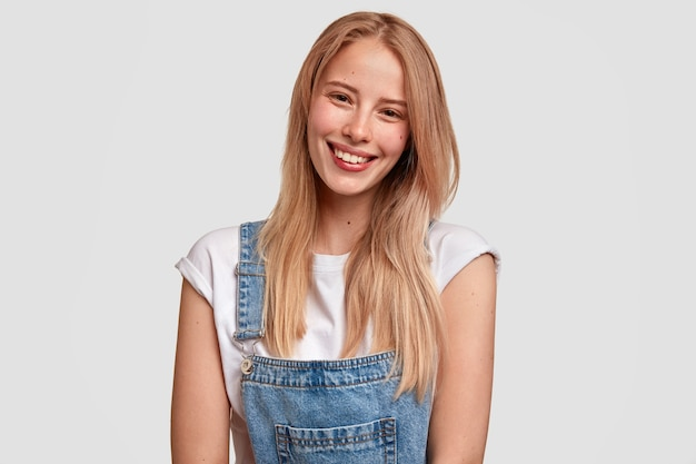 Glad european young woman with satisfied expression, smiles broadly, has healthy pure skin, dressed in denim stylish overalls