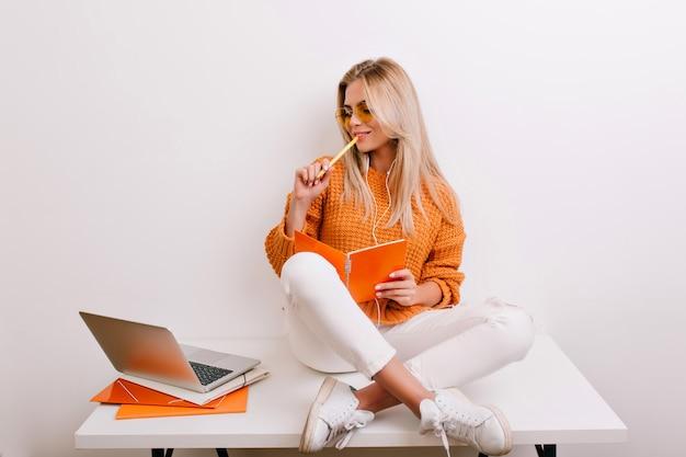 Felice donna bionda in abito alla moda che fa il suo lavoro in ufficio, tenendo il taccuino e la penna
