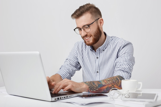 Glad fashionable man with smile, types on generic laptop, checks e mail or messages online