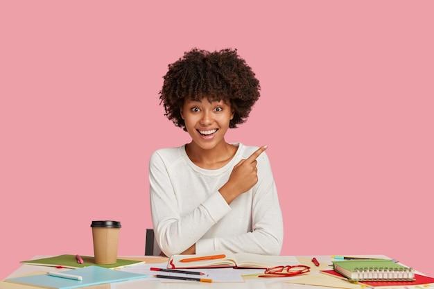 Felice architetto o designer femminile disegna uno schizzo nel taccuino, si siede al desktop con le cose necessarie per il lavoro
