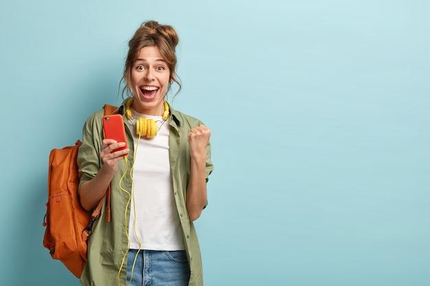 Felice blogger femminile stringe il pugno, si sente eccitata dalle statistiche sulla pagina web nei social network, usa il cellulare e le cuffie, indossa jeans e camicia cachi, trasporta lo zaino, isolato sul muro blu