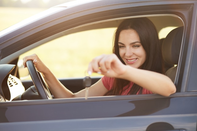 Glad female driver holds keys from car