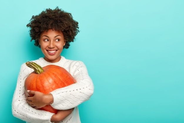 Glad female has afro haircut, holds big pumpkin, uses healthy product for preparing organic meal, looks happily away, dressed in sweater
