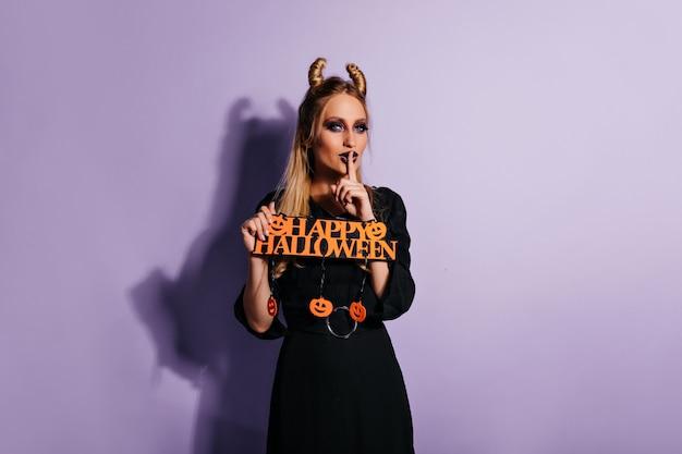 Радостная женская модель в элегантном черном платье позирует в хэллоуин. милая девушка в костюме ведьмы, стоя на фиолетовой стене.