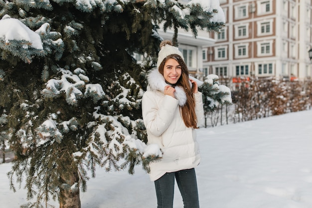 公園の散歩中に冬の日を楽しんでいる流行の服装でうれしい女性モデル。凍るような1月の日に路上で時間を過ごし、笑う笑う女性の屋外のポートレート。