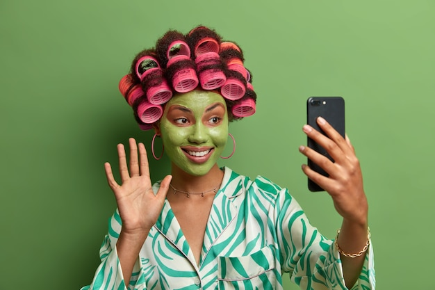 Felice modello femminile con maschera facciale verde, palmo ondeggiante e saluta un amico, ha una videoconferenza tramite un moderno smartphone, indossa bigodini per fare un taglio di capelli perfetto, vestito con abiti casual