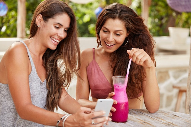 Glad female models choose photo to update in social networks, view images on smart phone with happy expressions