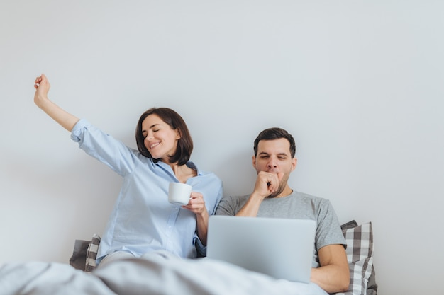 Glad female stretches in bed, drinks hot coffee and her husband works all night on laptop computer