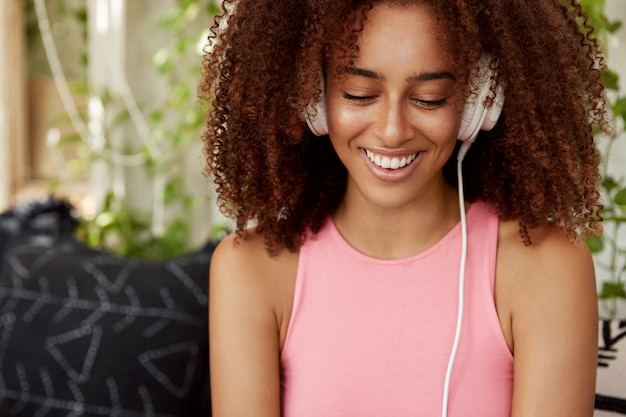 Glad female student with dark skin, listens audio book in headphones, connected to unrecognizable device. pretty young woman relaxes cool music, sits against cafeteria interior, enjoys leisure time