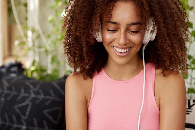 Радостная студентка с темной кожей, слушает аудиокнигу в наушниках, подключенных к неузнаваемому устройству. довольно молодая женщина расслабляется классной музыкой, сидит на фоне интерьера кафетерия, наслаждается досугом