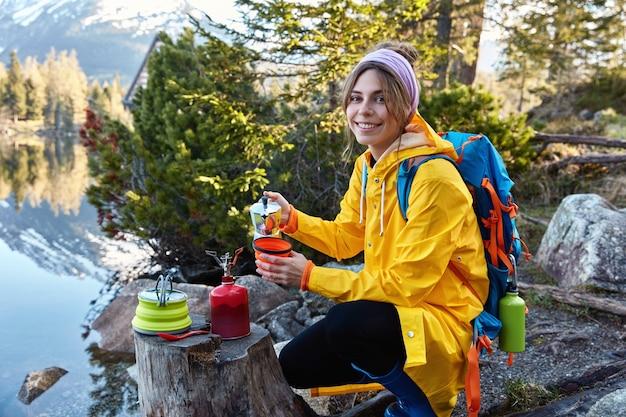 嬉しい女性観光客がコーヒーメーカーから熱い香りのよい飲み物を注ぎ、キャンプの冒険をしています