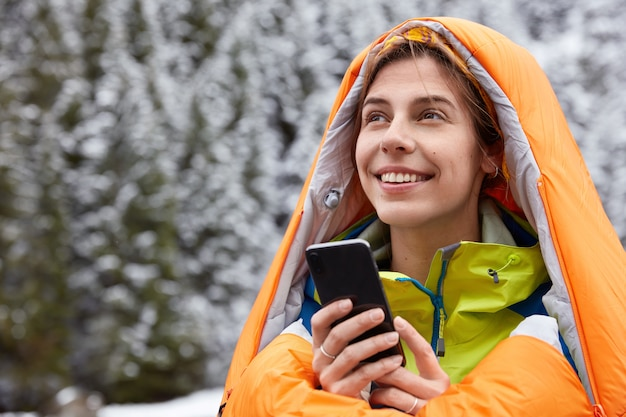 嬉しい女性旅行者は寝袋で暖まり、雪に覆われた山の頂上でポーズをとり、現代の携帯電話を持っています