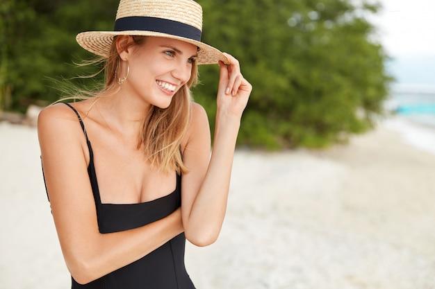 明るく楽しい笑顔の女性、夏用の帽子と水着を着て、ビーチで屋外でポーズをとり、健康な肌を持ち、気分が良く、遠くに元気に見えます。人と休息のコンセプト