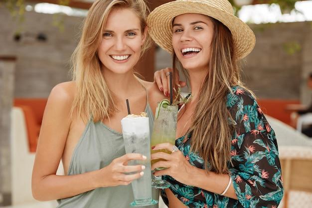 Le femmine felici si abbracciano e hanno un aspetto positivo, si ricreano insieme nel luogo di villeggiatura, festeggiano l'inizio delle vacanze al bar con cocktail, esprimono piacevoli emozioni. persone, riposo, stile di vita, positività