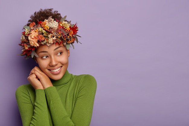 嬉しいフェミニーの女の子は目をそらし、快適な服と植物の花輪を着て、心地よく微笑む