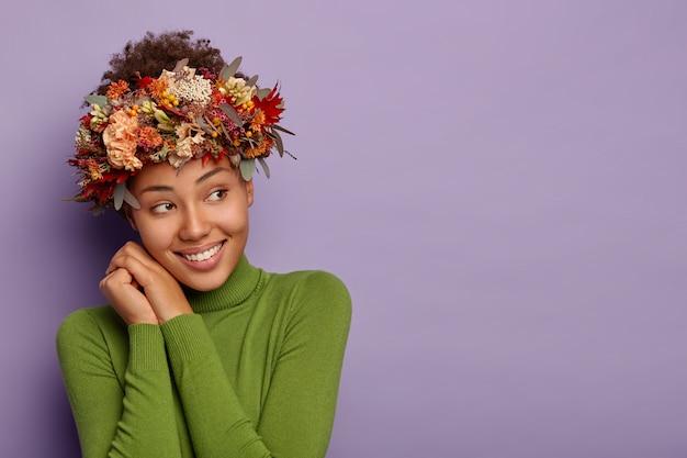 La ragazza femminile felice distoglie lo sguardo, indossa abiti comodi e ghirlande di piante, sorride piacevolmente