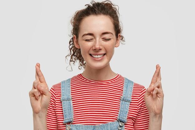 Felice giovane femmina lentigginosa chiude gli occhi, ha un ampio sorriso, incrocia le dita come desidera, vestita con maglietta a righe rosa e salopette, sta in piedi contro il muro bianco. la donna prega per il meglio.
