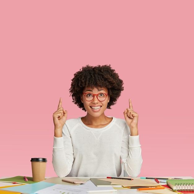 満足のいく表情でうれしいフリーランサー、丸い眼鏡をかけ、両方の人差し指を上に向け、デスクトップに座って、持ち帰り用のコーヒーを飲み、気分が良い。人