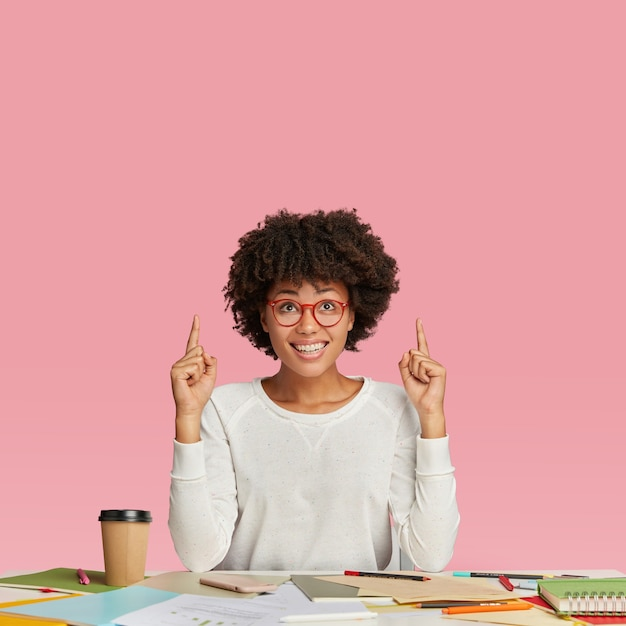 Libero professionista felice con espressione soddisfatta, indossa occhiali rotondi, punta con entrambi gli indici verso l'alto, si siede alla scrivania, beve caffè da asporto, è di buon umore. persone