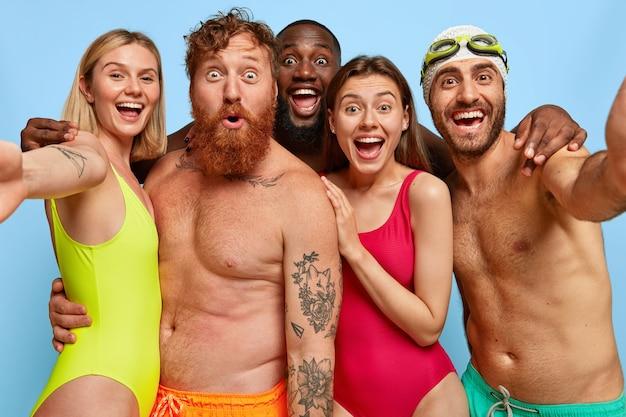 Amici contenti che posano in spiaggia