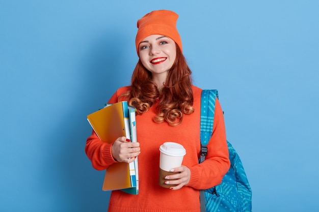 嬉しい生姜女子学生は講義後にコーヒーブレイクをし、温かい飲み物を楽しみ、背中にリュックサックを持っています