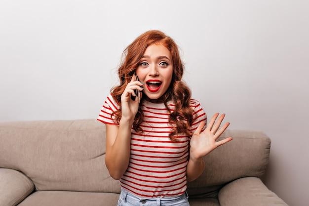 驚いた笑顔で電話で話しているうれしい生姜の女性。スマートフォンでソファに座っているポジティブな白人の女の子の屋内写真。