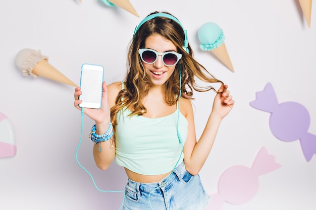 Glad girl in blue accessories listening music in her room, holding smartphone and playing with hair. portrait of elegant young woman in glasses with curly amazing hairstyle posing on purple wall.