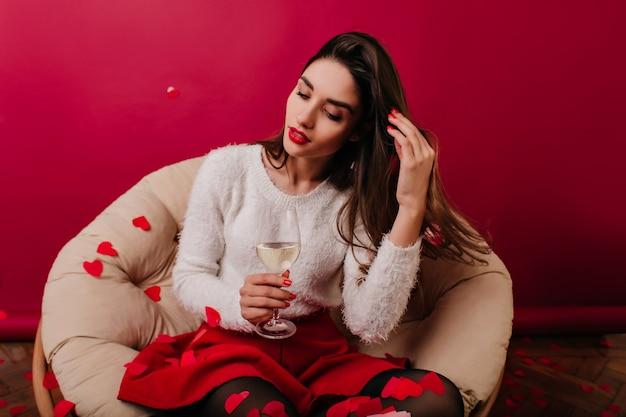 Счастливая девушка в стильном свитере, глядя на стакан воды