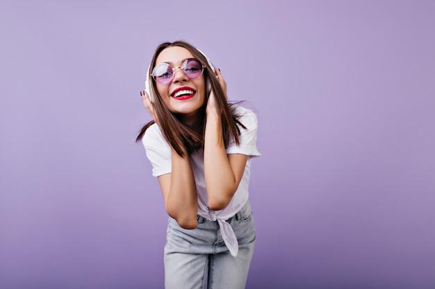 Рад девушка в солнцезащитных очках, касаясь ее наушников с улыбкой. внутреннее фото шикарной женской модели в изолированных джинсах.