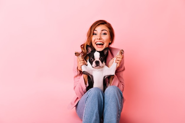 Glad girl in jeans playing with funny little dog. indoor portrait of excited ginger lady with curly hairstyle spending time with her puppy.