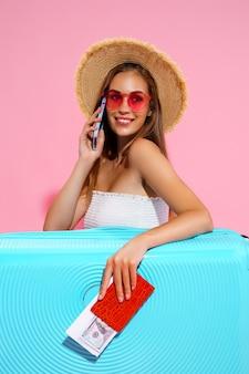 Довольная девушка с чемоданом, билетами, деньгами и паспортом собирается путешествовать, бронируя отель по телефону