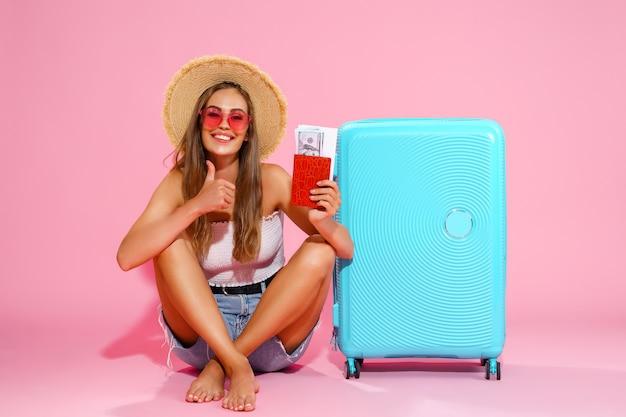 Довольная девушка с чемоданом, билетами, деньгами и паспортом собирается путешествовать, пока жесты пальцем вверх