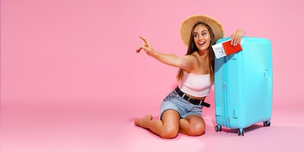 Счастливая девушка с чемоданом, билетами, деньгами и паспортом собирается путешествовать, указывая пальцем