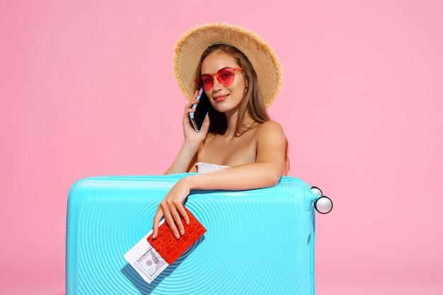 Довольная девушка с чемоданом, билетами, деньгами и паспортом собирается путешествовать, разговаривая по телефону