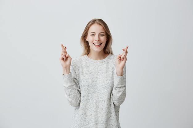 Рад, что счастливая блондинка носит свитер, широко улыбается, скрещивает пальцы, надеется на удачу