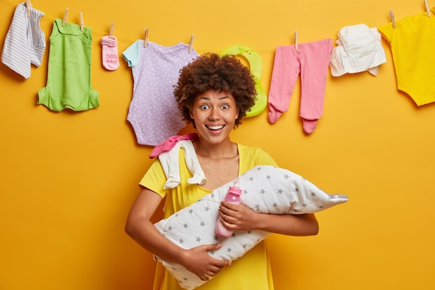 Glad happy mum embraces her little infant, holds bottle with nipple and feeds baby, nursing newborn, prepares artifical feed, stands against yellow wall, washed childs clothing hanging on rope
