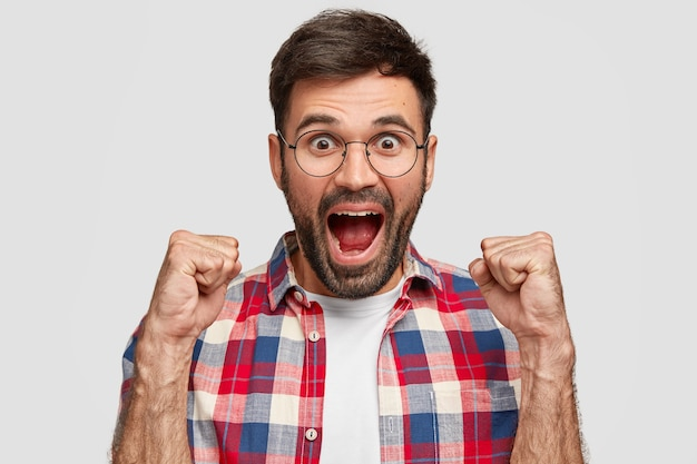 Glad happy young male opens mouth, clenches fists and exclaims with triumph, dressed in checkered shirt, stands against white wall. man with stubble feels like champion or winner