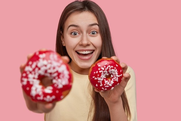 Glad happy young woman has broad smile, being in high spirit, carries tasty dessert, focus on douchnuts, wears casual clothes, isolated over pink background. people