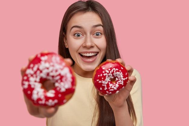 Радостная счастливая молодая женщина имеет широкую улыбку, находится в приподнятом настроении, несет вкусный десерт, сосредотачивается на douchnuts, носит повседневную одежду, изолированную на розовом фоне. люди