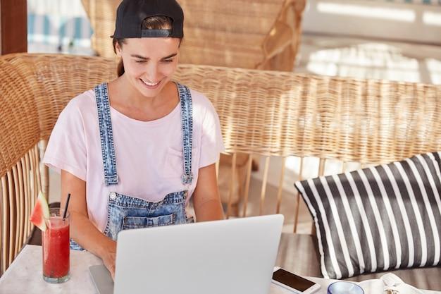 Довольная хипстерская женщина с веселым выражением лица, в кепке и джинсовом комбинезоне, сидит перед открытым портативным компьютером, пьет свежий летний коктейль, наслаждается онлайн-общением и бесплатным доступом в интернет.