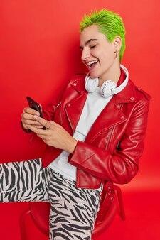 Радостная хипстерская девушка с крашеными зелеными волосами пользуется мобильным телефоном, отправляет сообщения друзьям, устраивает встречи, жизни беззаботная жизнь наслаждается молодежью, использует крутое приложение на сотовой связи, сидит на стуле, слушает популярную музыку