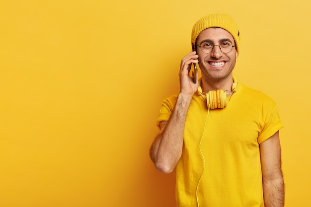 Felice ragazzo hipster con un aspetto piacevole, sorride positivamente, parla tramite smartphone, vestito con abiti casual, indossa occhiali trasparenti, discute le ultime tendenze della moda con il migliore amico