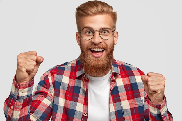 Glad hipster with funny expression, clenches fists, celebrates successful day, has trendy hairstyle and ginger beard, wears bright checkered shirt, isolated over white wall. triumph concept