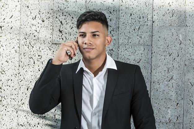 Glad hispanic entrepreneur speaking on smartphone