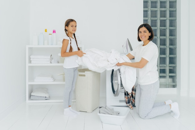 Glad housewife does washing with little adorable helper. mother and daughter wash clothes in laundry room, load linen in washer. woman stands on knees near washing machine. housework concept