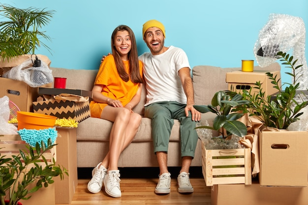 Glad husband and wife look with happiness, hug while sit on sofa in living room, move to new home, cardboard boxes around