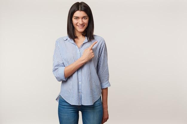 Felice e ispirata giovane bruna guarda con felicità e sorriso e punta il dito indice lì sullo spazio della copia, vestito con una camicia, isolato