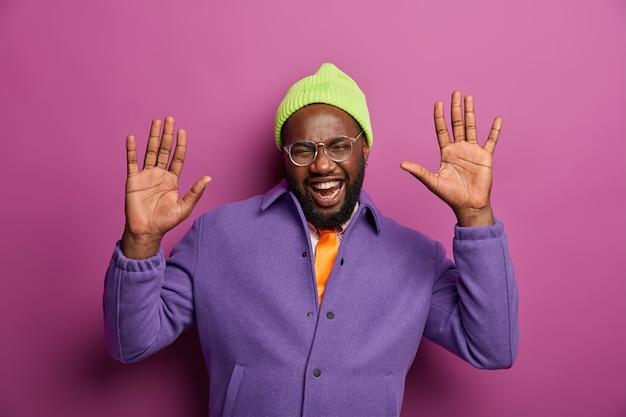 기쁘고 즐거운 아프리카 계 미국인 남자는 손바닥을 들어 올리고, 즐겁게 웃고, 즐겁고, 친구와 자유 시간을 보내고, 긍정적 인 감정을 표현하고, 녹색 모자를 쓰고 있습니다.
