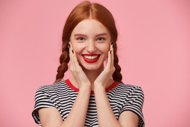 Glad joyful beautiful red-haired girl with two braids keeps hands near her face and smiling happily with red lips, showing white healthy teeth, isolated
