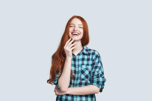 회색 배경 위에 서서 웃고 있는 아름다운 빨간 긴 머리를 가진 기쁘고 즐겁고 평온한 소녀